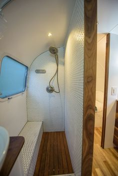 Gorgeous bathroom shower design and built by Townsend Travel Trailers. Teak floors and hexagon tile make for a great combination in this renovated vintage airstream trailer.