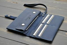 Purse / wallet leather handmade.     Classic leather wallets for men and women who like to order and comfort!     Purse made of excellent leather. It consists of three long compartments for paper money, as well as telephone and 4 pockets for plastic cards, business cards, badges, and other travel documents. Closes purse strap on a mechanical button. Also, the purse has a strap on the wrist. Purchase and use a pleasure!   Material: genuine leather. Size: 19,5-10 cm Color - black, brown, blue…