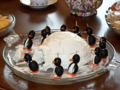 Igloo made out of a cheese ball and penguins made of olives and cream cheese