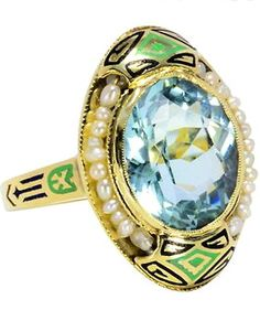 Art Deco ring with an oval faceted aquamarine, approx 4.1 carats, in a a yellow gold collet set with 24 natural freshwater seed pearls. North and south intriguing designs of inky black, spring green and Prussian blue enamel accent the ovoid shape. Enamel side embellishments which echo the pattern on the front are inlaid in enamel down the shank. Circa 1925.
