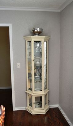 This is the exact curio cabinet I used to have. This one has been painted a lovely cream color; the one I had was a dark walnut. I sold it because it didn't match my decor anymore, but I wish I had thought of repainting it!!!