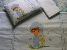 Jogo de lençol para berço pintado com acabamento de primeira linha.    Composto por:  -1 lençol pintado medindo 1,65 comp x 1,10 larg  -1 lençol de elástico medindo 1,30 comp x 0,70 larg x 0,12 de alt  -1 fronha pintada medindo 0,27 comp x 0,35 larg  -Acompanha travesseiro na mesma medida.    Lençol pintado em tecido branco 100% algodão com acabamento em tecido de bolinha azul e bordado inglês.Possui ainda duas faixas bordadas para decorar a pintura.O fronha acompanha o modelo do lençol.O…