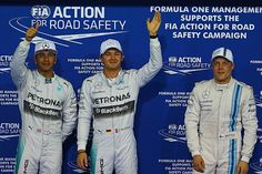 R19Q: Mercedes-AMG's German driver Nico Rosberg (C), Mercedes-AMG's British driver Lewis Hamilton (L), and Williams' Finnish driver Valtteri Bottas celebrate in the parc ferme after the qualifying session at the Yas Marina circuit in Abu Dhabi