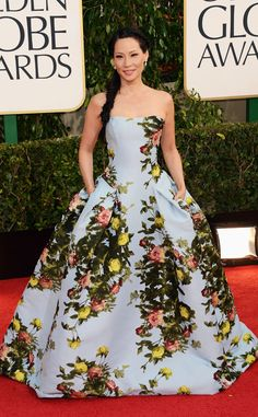 """2. Lucy Liu from The Top 10 Riskiest Looks at the 2013 Golden Globe Awards  """"I thought it was quite different than the metallic we did at the Emmys,"""" the star said of her 2013 Golden Globes look that featured a rose bush print. She chose to wear a side braid and Lorraine Schwartz earrings to complement the strapless Carolina Herrera gown."""