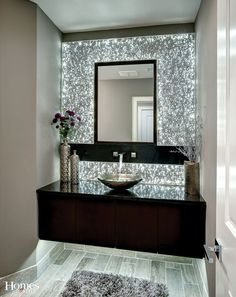 The centerpiece of this spectacular powder bath is the L.E.D. backlit extruded aluminum wall panels which give this room an ambiance that is unparalleled. The floating vanity with accent lighting, an amazing art glass vessel sink, beautiful solid surface top, and designer faucets flowing from the wall complete this one-of-a-kind room.:
