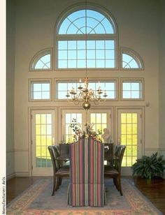 This Dining Room With High Ceiling Gets Lots Of Light And Beauty From The  Four French Doors Plus The Gridded Windows Above, Including The Pie Shaped  Side ...