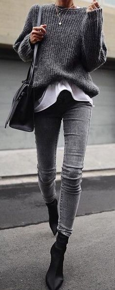 #spring #outfits woman in black sweater, black leather crossbody bag, and grey denim jeans walking on concrete pathway during daytime. Pic by @speak__style #walkingoutfit