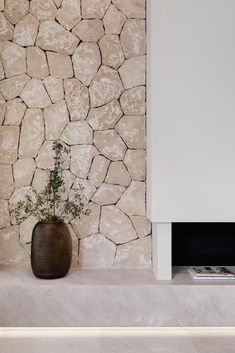 A stone wall and hidden lighting are unique design elements of this modern living room.