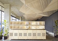the geometric ceiling of melbourne's assemble studio is comprised of triangular, origami-like folds of timber battens.