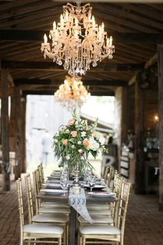 Hi-low. Rustic barn is glamorously set with gold chiavari chairs and crystal chandeliers. Centerpieces of pink tulips, apricot roses, hydrangea and lots of greenery have an unstructured elegance.    Glamorous, Vintage, Rustic Texas Barn Wedding | Venue: Cherokee Rose