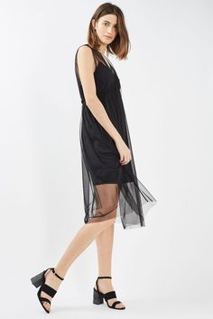 Tulle is taking over our wardrobes, detailed here on this pretty midi dress. In a chic black, it comes in a sleeveless style with a slip underneath. Layer over a graphic tee for a unique take on the look. #Topshop