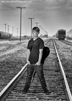 Senior Portraits With Guitars | senior pictures taken by train tracks in a black and white photo with ...