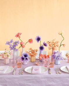 A scattering of single-flower arrangements like sweet peas, poppies, and anemones in colorful bottles makes for an informal yet impactful tablescape.