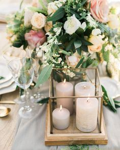 Unexpected design pairings can make a table setting unique. Flowers Living proved this by placing round taupe pillars into a cube display case. The pastel color palette made the various elements feel cohesive. Romantic Table Setting, Romantic Wedding Centerpieces, Rustic Wedding Flowers, Outdoor Wedding Decorations, Candle Centerpieces, Wedding Table Settings, Wedding Table Numbers, Candles, Unique Flowers
