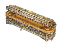 AN IMPRESSIVE ANTIQUE INDIAN DIAMOND, RUBY, EMERALD AND ENAMEL GOLD PEN BOX  The octagonal-shaped hinged box on scrolling feet, applied with blue, red, white and green enamel and set with rubies, emeralds and table-cut diamonds, the lid centering on a gold crest depicting Krishna as Govind Devji, flanked with the Insignia of The Most Exalted Order of Star of India, opening to reveal four inkpots and a removable pen tray, Jaipur, circa 1880, 27.5 cm long