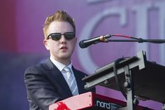 lead singer, wearing a smart jacket and shirt, more formal look to look sophisticated and smart