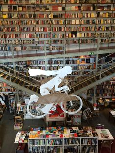 Gorgeous library display of person riding bike suspended above collection