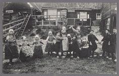 Een groep kinderen in Marker dracht spelen op een grasveldje voor het huis. 1900-1906 #NoordHolland #Marken