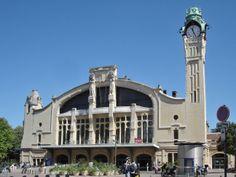 Gare de Rouen par Adolphe Dervaux. Son chantier commence en 1913. La structure, en béton armé, est due au bureau d'étude Considère, Pelnard et Caquot. La Première Guerre mondiale va retarder l'avancement des travaux qui vont durer jusqu'en 1928. Le bâtiment est monumental dans un style Art nouveau tardif, auquel s'ajoute l'affirmation moderniste d'une structure en béton apparente. La tour de l'horloge a une hauteur de 37 mètres.