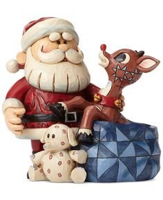 Rudolph's nose lights up as he pops out of a toy bag to surprise Santa while they joyfully prepare for the magical night. This Santa with Rudolph collectible figurine is beautifully crafted in the fol