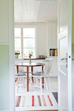 The round table, the white chairs, the floor, the rugs.  Swedish summer cottage