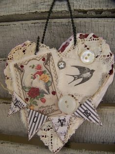 Vintage-style Valentine heart ornament with a wire hanger topping a painted, distressed base ~ embellished with vintage lace, tattered fabric images, buttons, rhinestone, and a tiny glittered banner