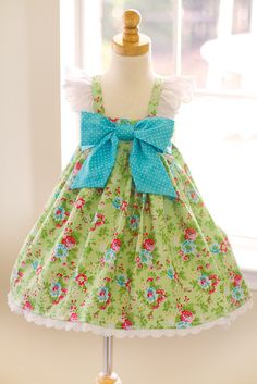 Meadow Blooms Dress – Kinder Kouture. The dress has an elasticized back and large bow that adorns the front of the dress.  The straps button for easy access. A Sara Norris design.