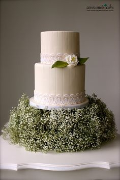 Adore this! A simple wedding cake wrapped with lace trim, accented with a single garden rose, sits atop a cloud of babys breath