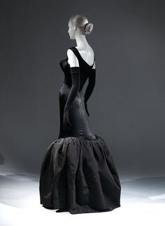 The challenge of this design, as James noted, was to achieve an elegant effect despite the difficulty of mounting a voluminous flounce of stiff faille on a narrow sheath of supple black satin. An organza underlining supporting the satin and an interior horsehair roll causing the fountain-like upward lift of the tulip flounce contributed to its artistic resolution