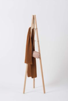 Artek Kiila Coat Stand - Composed of three wood legs and the signature Kiila wedge, the Kiila Coat Stand is simple and sturdy.   Inspired by the camera tripod on which designer Daniel Rybakken used to hang his coats, it has a low centre of gravity and can accommodate serious weight without tipping over.