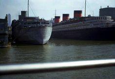 RMS Queen Elizabeth in battleship gray,next to the SS Normandie
