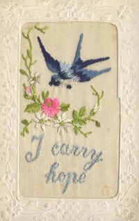 "An embroidered postcard with a blue bird flying towards a curved line of pink and white flowers, below which are the words ""I carry hope"". sent by a soldier in the first WW to his loved ones at home"