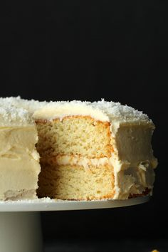 Fabulously coconutty two layered vegan coconut cake topped with a decadent coconut rum frosting. Super easy, moist, fluffy and dense at the same time (I know!) this delicious vegan cake is a total delight to the tastebuds!  lovingitvegan.com