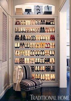 A lighted shelving unit displays an enviable collection of heels. We'll take it! - Traditional Home ® / Photo: Luca Trovato / Design: Tim Clarke