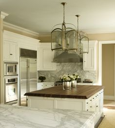 butcher block island......kitchens - yellow gold walls white kitchen cabinets marble countertops white kitchen island butcher block countertops brushed nickel pendants lanterns