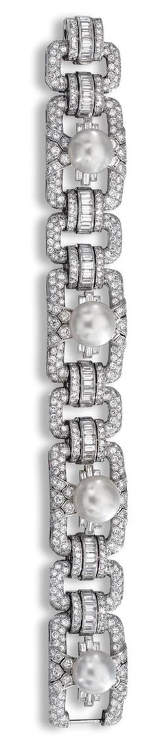 CULTURED PEARL AND DIAMOND BRACELET.  Designed as a series of button cultured pearls set within a open work surround of brilliant-cut diamonds, spaced by single-cut and baguette stone links, mounted in platinum,  length 195mm.
