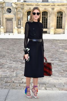 At the Dior show Olivia chose unexpected accessories like a scarf bracelet, subtly striped oxblood bag, and tassel-embellished shoes.
