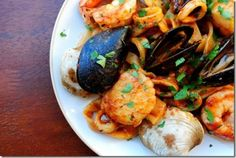 1 Tablespoon extra virgin olive oil  2 cloves garlic, minced  2 sea scallops  2 large, peeled & deveined shrimp  4 little neck clams, scrubbed  4 mussels, scrubbed  1 squid tube, cut into rings  1/3 cup white wine  1/3 cup marinara sauce