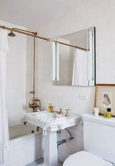 Chic, elegant bathroom features drop-in bathtub clad in subway tiles as well as brass, exposed plumbing, shower kit adorned with white ruffled shower curtain situated next to frameless, folding  mirror over pedestal sink accented with brass faucet kit.