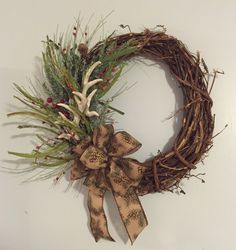 This distressed grapevine wreath has all the charm to get you through the winter months. Adorned with faux deer antlers and greenery that looks like its plucked straight out the forest. A brown bow finishes it off with sparkling pine cones.