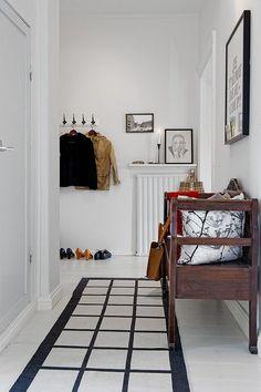 Banco de madera con cojines y alfombra en pasillo