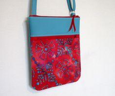 Pochette confectionnée en simili cuir turquoise et tissu batik rouge et turquoise.Le dos de la pochette est en simili cuir turquoise. Vous trouverez une poche zippée de 18 cm su - 17930932