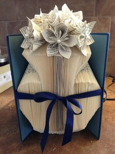 """This is one of the first books I folded. I used a grid and drew my vase. As I worked, I altered my pattern to achieve a balanced image. The origami flower tutorial is on my """"Book Art Tutorial"""" board."""
