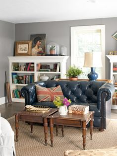 Chesterfield couch, Union Jack pillow, vintage prints, bookshelf styling, grey walls, living room