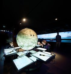 Exhibition basement 'Reede van Texel'. A Globe and installation of maps. Every map tells the story of a sea journey starting at Texel. (photograph by Thijs Wolzak)
