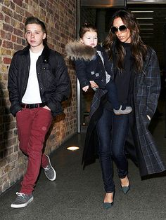Victoria Beckham in a long grey checkered coat + black sweater + skinny jeans + grey heels