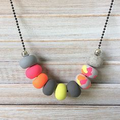 Handmade multi coloured bright pink, orange, yellow and grey coloured bead necklace. Each polymer clay bead has been individually hand rolled, giving them character. All strung on 28in long black steel ball chain.  This is an original piece and I only use quality materials Happy shopping Offering Free shipping within Australia