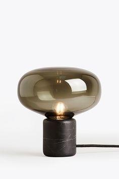 la lampe de table noire Karl-Johan réalisé par Digne Hytte, édition de New Works est fait en verre façon fumé et posé sur un support en marble noir