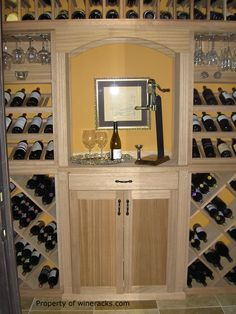 A custom wine cellar with display rows on the wine racks, an arch and tasting table. Find more at WineRacks.com