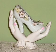 Pair of hands holding a slipper.